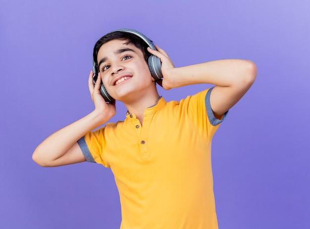 Souriant jeune garçon caucasien regardant la caméra en touchant les écouteurs isolé sur fond violet