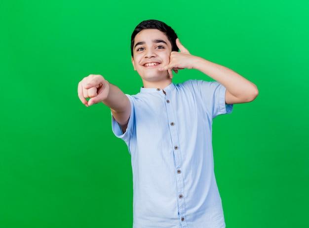 Souriant jeune garçon caucasien regardant et pointant vers la caméra faisant le geste d'appel isolé sur fond vert avec espace copie