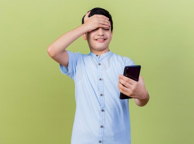 Souriant jeune garçon caucasien tenant et regardant le téléphone mobile en gardant la main sur le front isolé sur fond vert olive avec espace copie