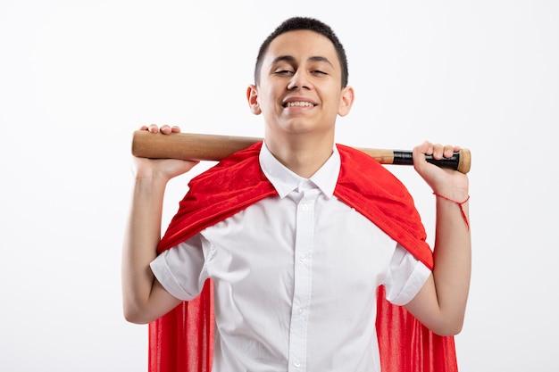 Souriant jeune garçon de super-héros en cape rouge tenant une batte de baseball derrière le cou en regardant la caméra isolée sur fond blanc