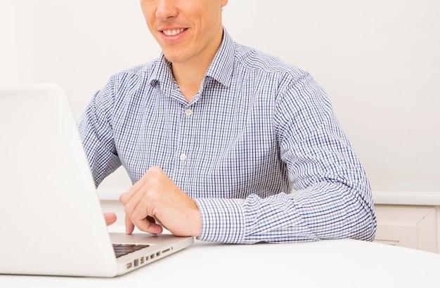 Souriant jeune homme d'affaires à l'aide d'un ordinateur portable sur une table blanche