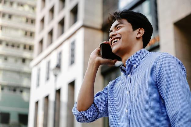 Souriant jeune homme d'affaires asiatique à l'aide de téléphone portable dans la ville