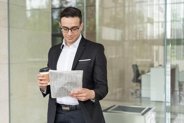 Souriant jeune homme d'affaires avec café lecture journal à l'extérieur