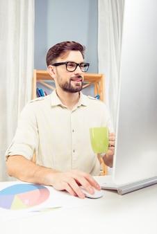 Souriant jeune homme d'affaires dans des verres et tasse travaillant avec ordinateur
