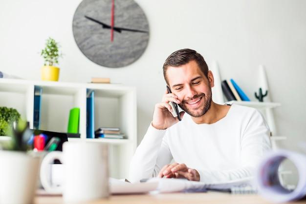Souriant jeune homme d'affaires parler sur smartphone