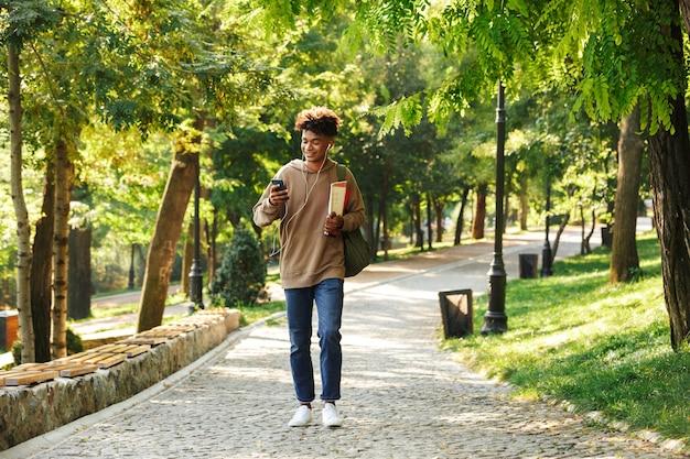 Souriant jeune homme africain avec sac à dos marchant