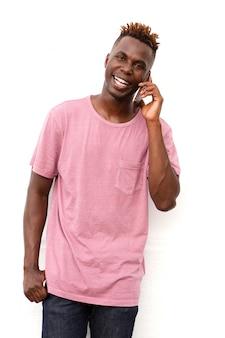 Souriant jeune homme afro américain debout contre le mur et faire un appel téléphonique