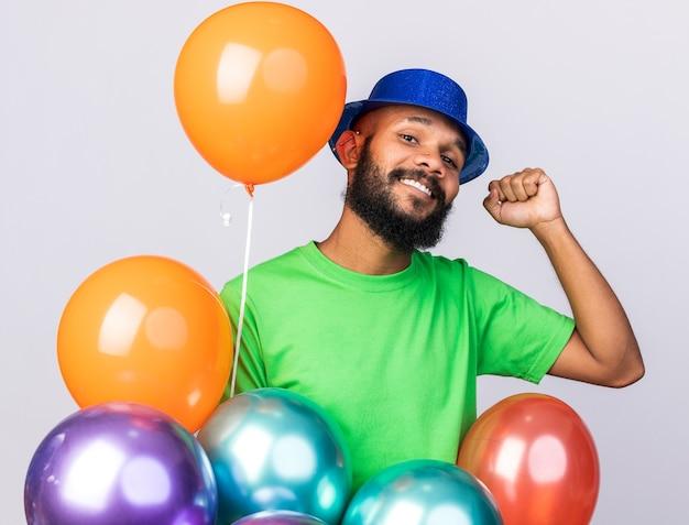 Souriant jeune homme afro-américain portant un chapeau de fête debout derrière des ballons montrant un geste oui isolé sur un mur blanc