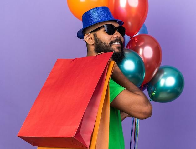 Souriant jeune homme afro-américain portant un chapeau de fête avec des lunettes tenant des ballons avec un sac-cadeau isolé sur un mur bleu