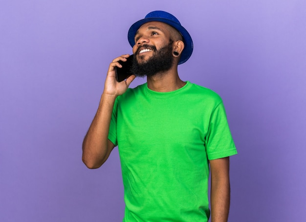 Souriant jeune homme afro-américain portant un chapeau de fête parle au téléphone