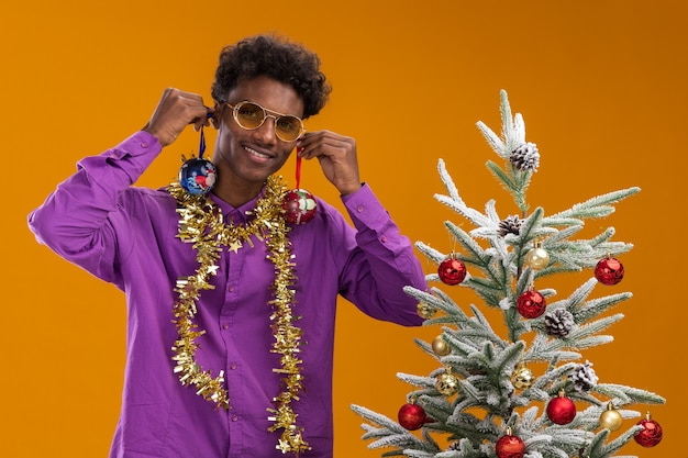 Souriant jeune homme afro-américain portant des lunettes avec guirlande de guirlandes autour du cou debout près de l'arbre de noël décoré suspendu des boules de noël sur les oreilles isolées sur le mur orange