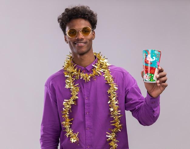 Souriant jeune homme afro-américain portant des lunettes avec guirlande de guirlandes autour du cou tenant une tasse de noël en plastique regardant la caméra isolée sur fond blanc