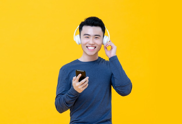Souriant jeune homme asiatique, écouter de la musique en ligne à partir de smartphone