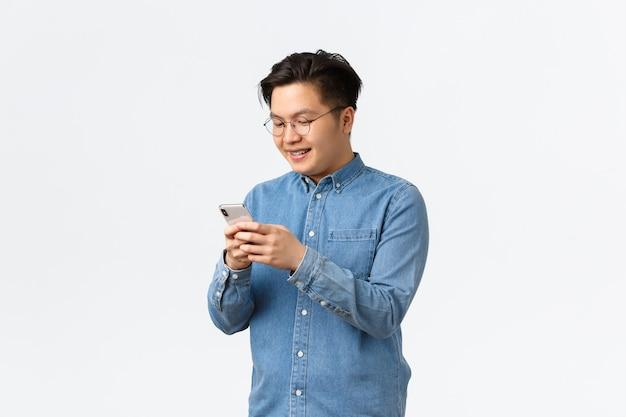 Souriant jeune homme asiatique faisant un message sur les réseaux sociaux, envoyant des sms à un ami à l'aide d'un téléphone portable. mec à lunettes, messagerie, jeu sur smartphone ou application de téléchargement, fond blanc