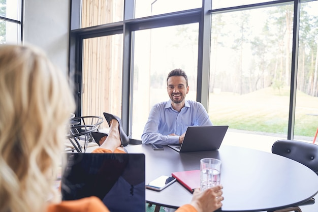 Souriant jeune homme assis à un bureau devant sa patronne blonde