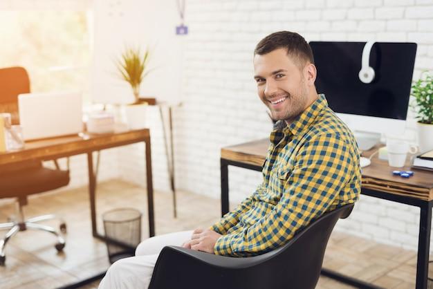 Souriant jeune homme assis sur une chaise de bureau.