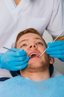 Souriant Jeune Homme Assis Dans Une Chaise De Dentiste Pendant Que Le Médecin Examine Ses Dents Photo Premium