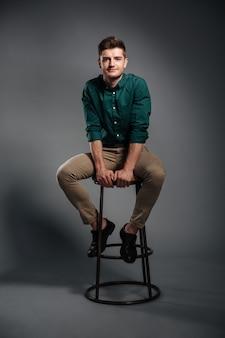 Souriant jeune homme assis isolé sur gris