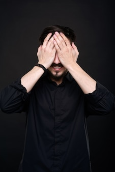 Souriant jeune homme avec barbe couvrant les yeux avec les mains en prévision de la surprise sur fond noir