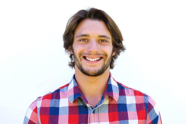Souriant jeune homme à la barbe debout sur fond blanc