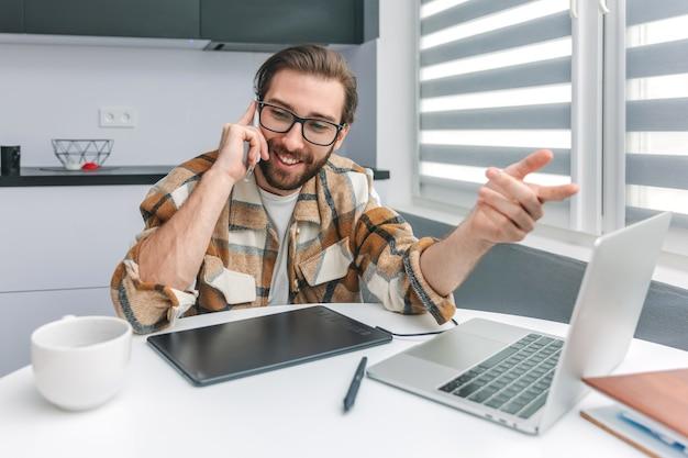 Souriant jeune homme à la barbe parlant au téléphone portable et faisant des gestes tout en travaillant à la maison