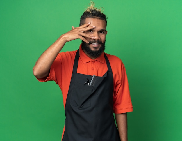 Souriant jeune homme barbier en uniforme gardant la main sur le visage regardant à l'avant à travers les doigts isolés sur un mur vert avec espace de copie