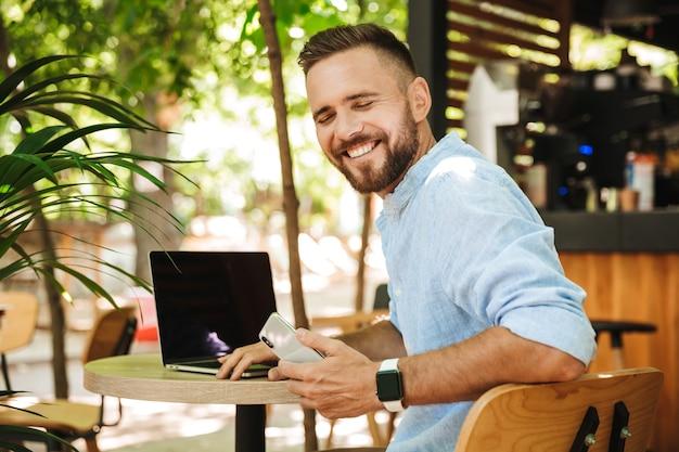 Souriant jeune homme barbu émotionnel à l'aide d'un ordinateur portable et d'un téléphone mobile