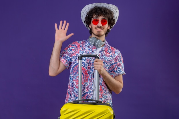 Souriant jeune homme beau voyageur bouclé portant des lunettes de soleil, des écouteurs sur le cou et un chapeau tenant valise faisant des gestes salut sur mur violet isolé avec espace copie