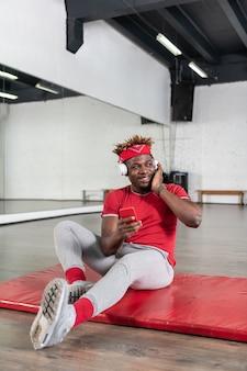 Souriant jeune homme bien formé reposant sur un tapis sportif tout en portant un t-shirt rouge
