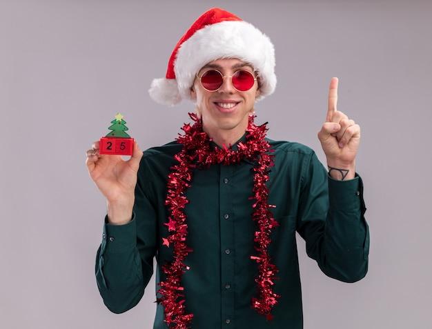 Souriant jeune homme blond portant un bonnet de noel et des lunettes avec une guirlande de guirlandes autour du cou tenant un jouet d'arbre de noël avec une date regardant la caméra pointant vers le haut isolé sur fond blanc