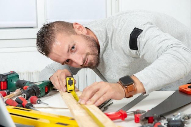 Souriant jeune homme bricolage à la maison