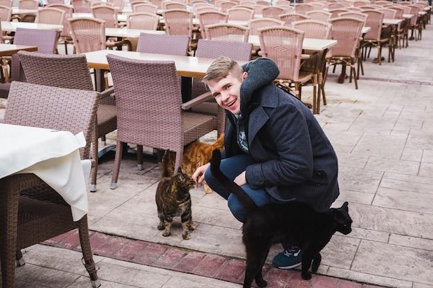 Souriant jeune homme caressant les chats errants.
