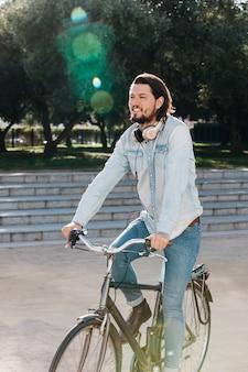 Souriant jeune homme avec un casque autour du cou à bicyclette dans le parc