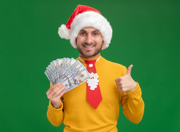 Souriant jeune homme caucasien portant chapeau de noël et cravate tenant de l'argent regardant la caméra montrant le pouce vers le haut isolé sur fond vert