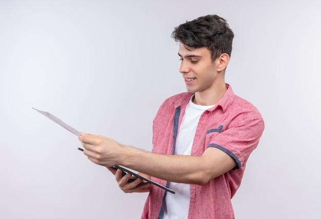 Souriant jeune homme caucasien portant chemise rose feuilletant le presse-papiers sur fond blanc isolé