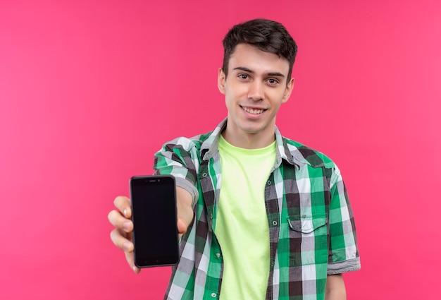 Souriant jeune homme caucasien portant une chemise verte tenant le téléphone à la caméra sur fond rose isolé