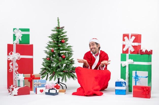 Souriant jeune homme célèbre le nouvel an ou les vacances de noël assis sur le sol près de cadeaux et arbre de noël décoré