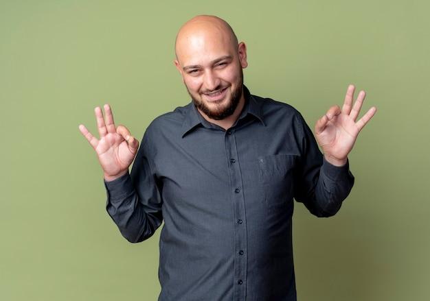 Souriant jeune homme de centre d'appels chauve faisant des signes ok isolés sur un mur vert olive