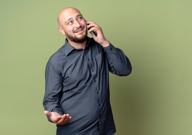 Souriant jeune homme de centre d'appels chauve montrant la main vide en levant et en parlant au téléphone isolé sur mur vert olive