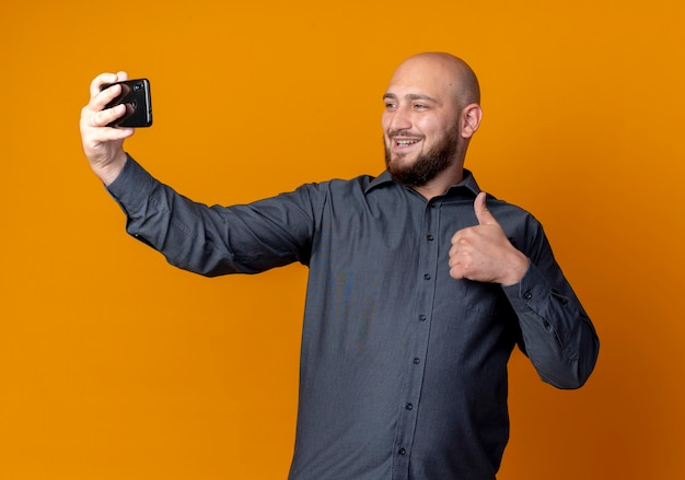 Souriant jeune homme de centre d'appels chauve montrant le pouce vers le haut et prenant selfie isolé sur mur orange