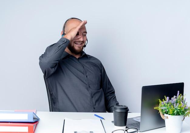 Souriant jeune homme de centre d'appels chauve portant un casque assis au bureau avec des outils de travail faisant le geste de regarder à l'ordinateur portable isolé sur le mur blanc