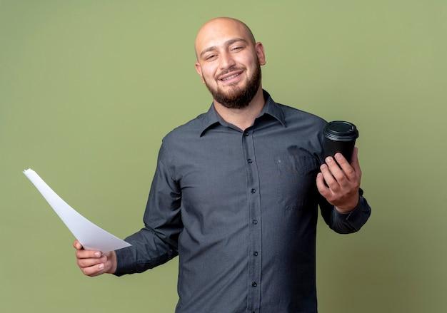 Souriant jeune homme de centre d'appels chauve tenant document et tasse à café en plastique isolé sur mur vert olive