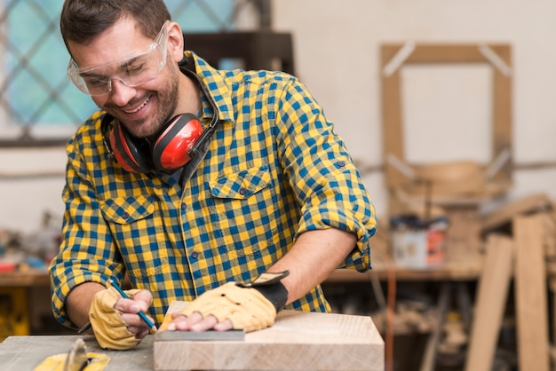 Souriant jeune homme charpentier travaillant avec du bois dans son atelier