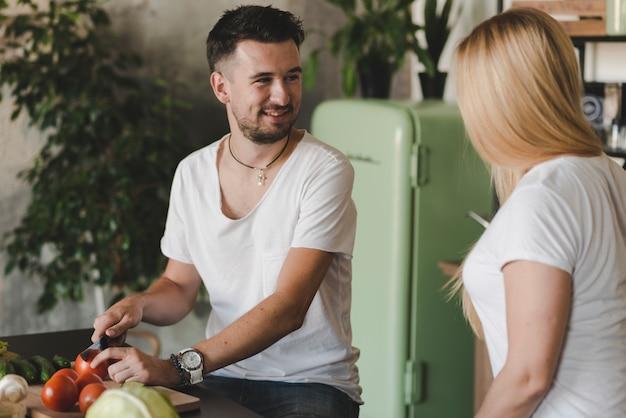 Souriant jeune homme coupe légumes regardant femme