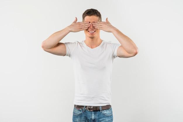 Souriant jeune homme couvrant ses yeux isolé sur fond blanc