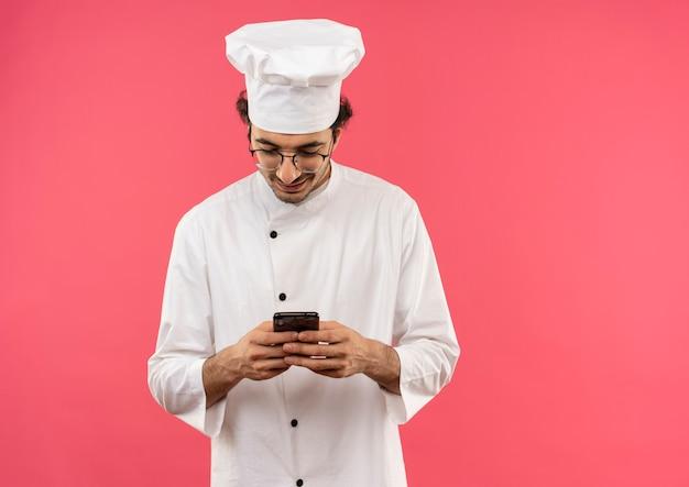 Souriant jeune homme cuisinier portant l'uniforme de chef et des lunettes de numérotation sur le téléphone isolé sur le mur rose