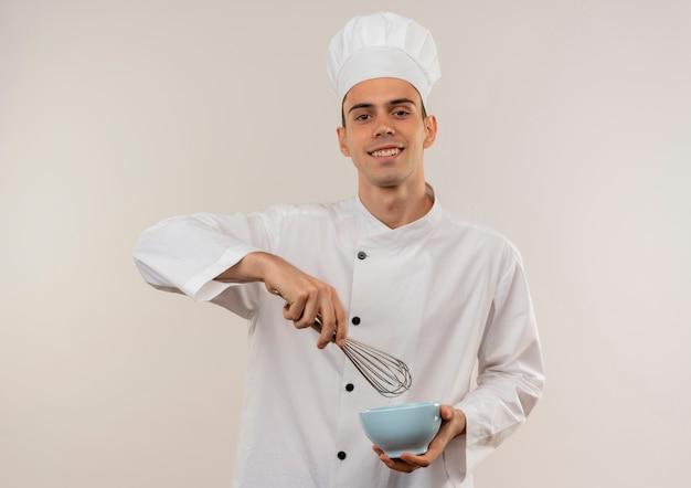 Souriant jeune homme cuisinier portant l'uniforme de chef tenant un fouet avec un bol
