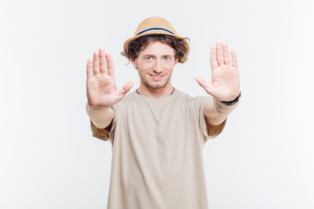 Souriant jeune homme dans un chapeau montrant le geste d'arrêt avec deux paumes sur fond blanc