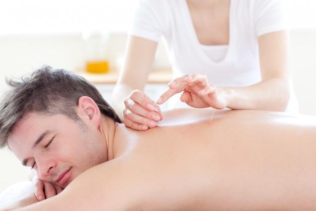 Souriant jeune homme dans une thérapie d'acupuncture