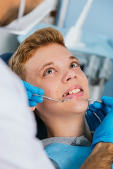 Souriant jeune homme est assis dans une chaise de dentistes pendant que le médecin examine ses dents